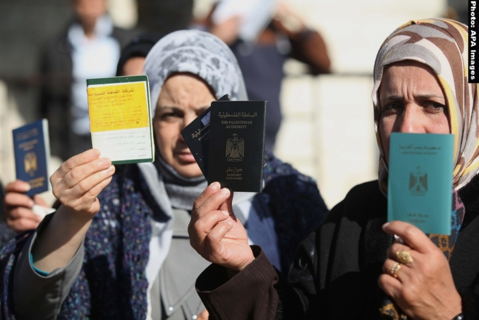Palestinian women hold their passports during a protest demanding for the opening of Rafah crossing border in front of the headquarters of the Council of Ministers in Gaza city, on December 31, 2014. Photo by Ashraf Amra