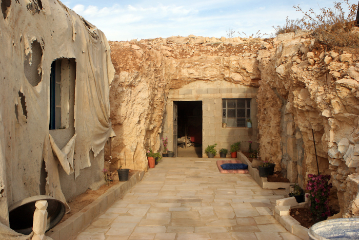 The entrance of the home cave was enlarged to place a door and a window. On the left, the family built a new brick house that is covered up by plastic as residents are prevented to build any structure by the Israeli Civil Administration